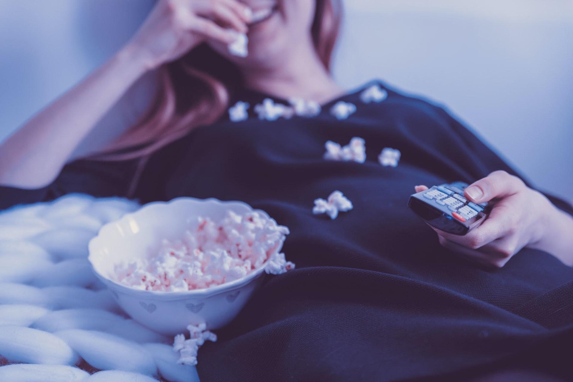 Serien und Filme Titelbild Frau mit Popcorn und Fernbedienung