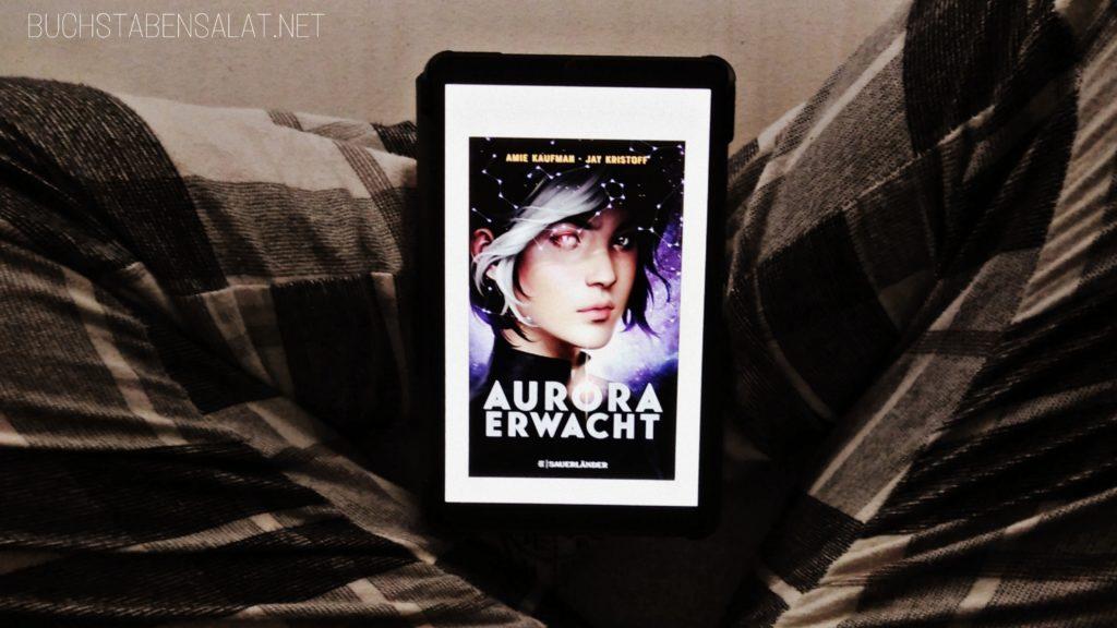 Aurora erwacht von Amie Kaufman und Jay Kristoff. Cover auf überkreuzten Beinen auf dem Tablet.