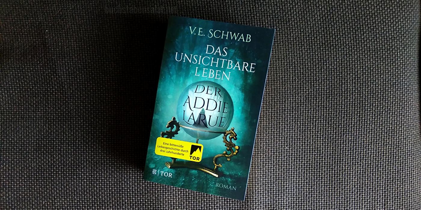 """Buchcover des Buches """"Addie LaRue"""" vor braunem Textil-Hintergrund."""