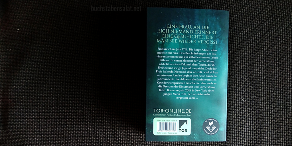 """Rückseite des Buches """"Das unsichtbare Leben der Addie LaRue"""" von V. E. Schwab vor braunem Textil-Hintergrund."""