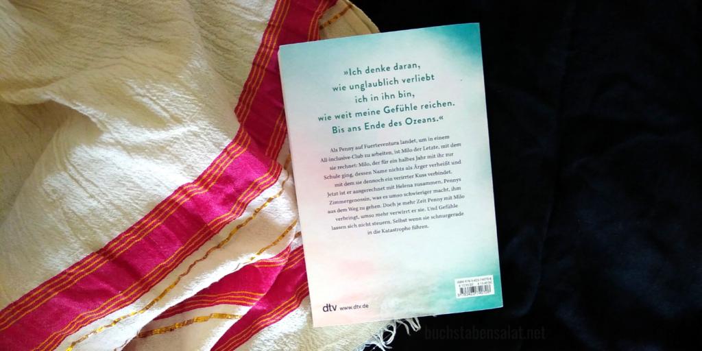 """Das Buch """"Mit dir leuchtet der Ozean"""" von Lea Coplin auf Textil. Dieses ist schwarz auf der rechten Seite und wird links überlappt von einem weißen, zerknitterten Tuch mit pinken und goldenen Streifen und Fransen. Man sieht die Rückseite des Buches mit dem Klappentext. Das Wasserzeichen des Fotos lautet """"buchstabensalat.net""""."""