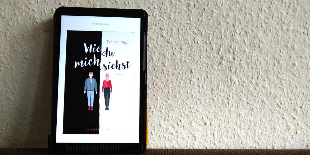 """Man sieht das eBook """"Wie du mich siehst"""" von der Autorin Tahereh Mafi auf einem Tablet vor einer weißen Rauhfasertapete. Es steht auf einem dunkelbraunen Textil und ist an die Wand gelehnt. Das Tablet ist links im Bild."""