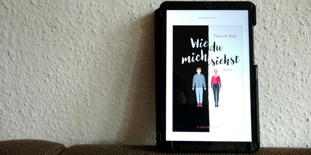 """Man sieht das eBook """"Wie du mich siehst"""" von der Autorin Tahereh Mafi auf einem Tablet vor einer weißen Raufasertapete. Es steht auf einem dunkelbraunen Textil und ist an die Wand gelehnt. Das Tablet ist rechts im Bild."""