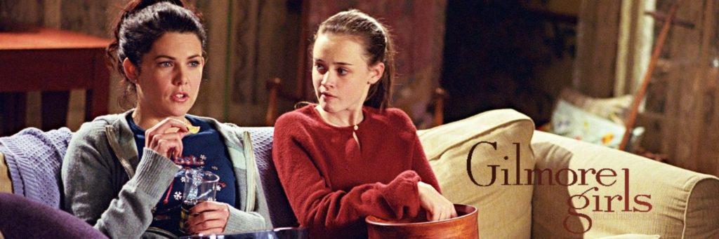 """Banner zur Serie """"Gilmore Girls"""". Abgebildet sind die beiden Hauptfiguren Lorelai und Rory Gilmore, mit Snacks auf dem Schoß beim Filmabend auf dem Sofa."""